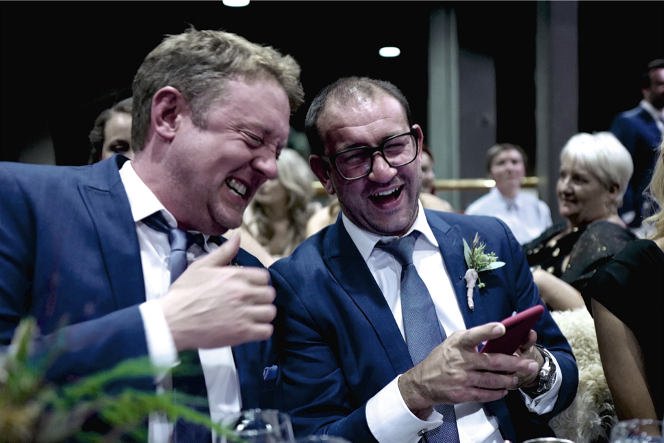 Photo of Ben Smith and Matt Watkinson formally dressed laughing at a mobile
